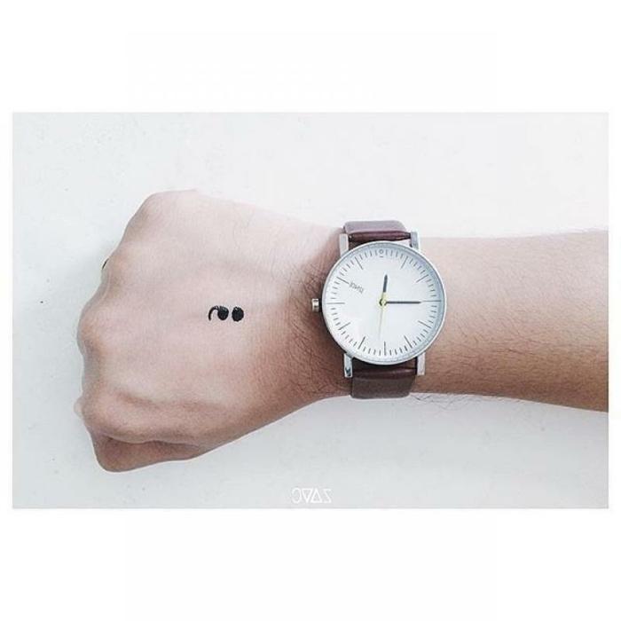 Bild von einer Hand mit einem Semicolon Tattoo und eine Uhr, geballte Hand, was bedeutet ein semikolon