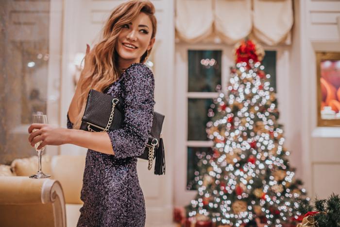 Glitzer Kleid für Silvester, schwarze Clutch, offene gewellte Haare, Weihnachtsbaum im Hintergrund
