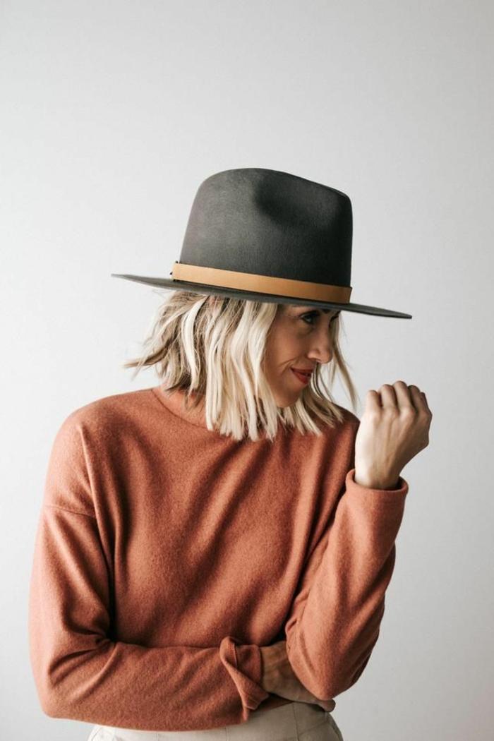 stylische Frau im ziegelroten Pullover, im grünen Filzhut, frisuren frauen kurz, hellblonde wellige Haare