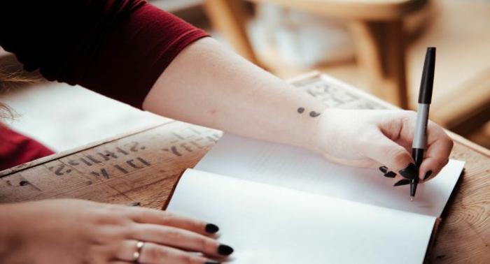 Schreibende Person mit einem Semicolon Tattoo am Arm, was bedeutet ein semikolon, schwarzer Nagellack