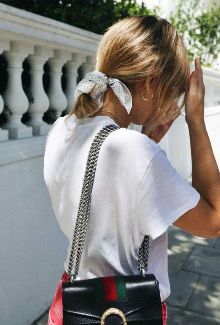 kurzhaarfrisuren frauen frech, dame im niedrigen haarknoten gebunden mit schal, weißes t-shirt und rote jeans, schwarte mini tasche mit silberne Henkel