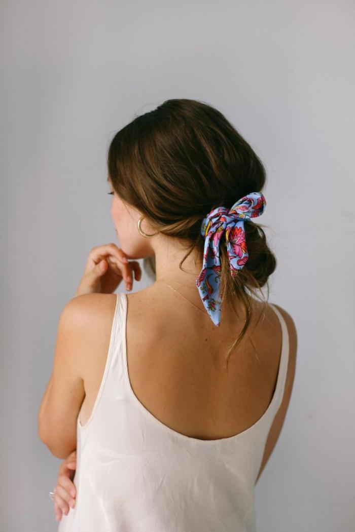 Frau mit braunen Haaren zu einem niedrigen und lockeren Haarknoten mit einem bunten Schal gebunden, goldene Ohrringe, weißes Top, Foto am weißen Hintergrund, Kurze Haare Frisuren
