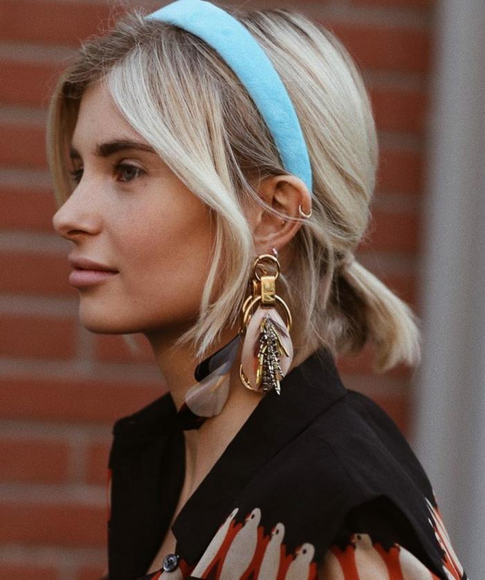 Haarreif in blau, blonde Kurzhaarfrisuren, effektvolle Ohrringe, hellblonde Frau, schwarze Bluse mit Tieren