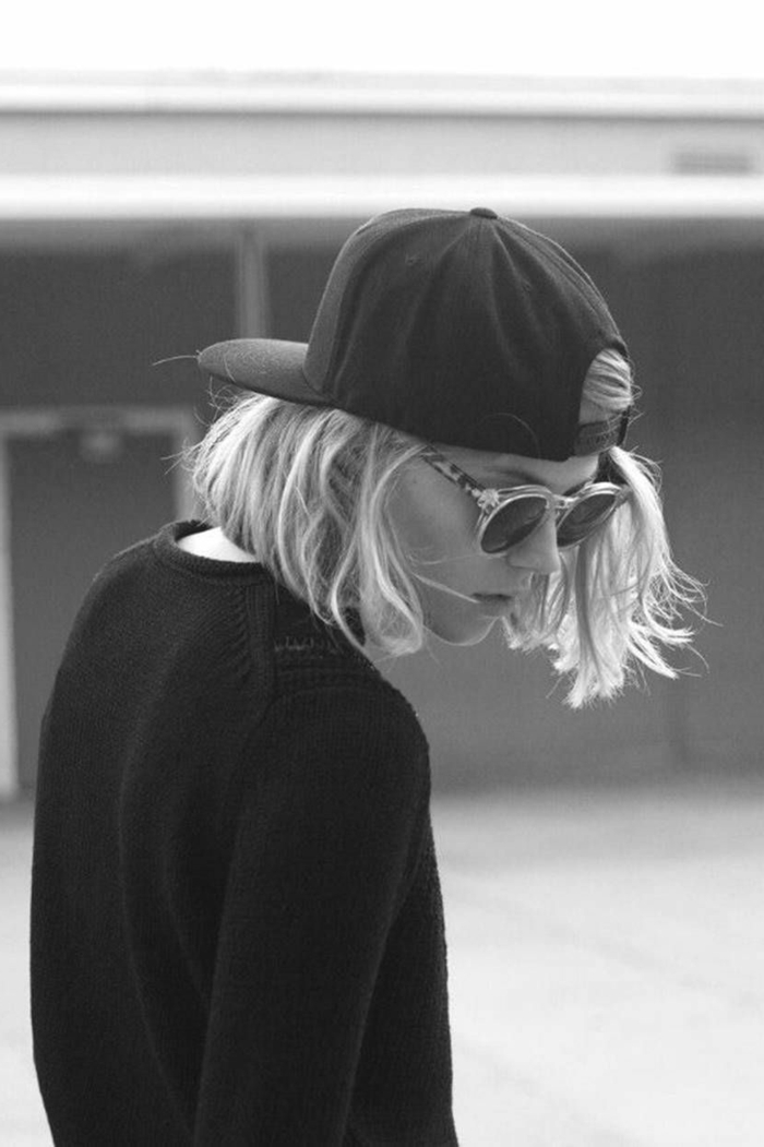 schwarz weiß Photo, Haarfrisuren kurz, schwarzer Pullover, schwarzer Hut mit Visier, runde Sonnenbrillen