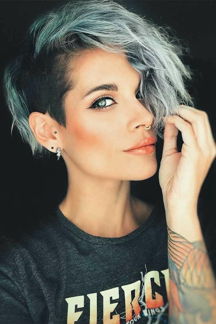 freche Kurzhaarfrisuren undercut, Piercings an der Nase und am Ohr, Haare in blaue Töne, bunte Tattoos am Arm, Geschminktes Gesicht mit Katzenaugen