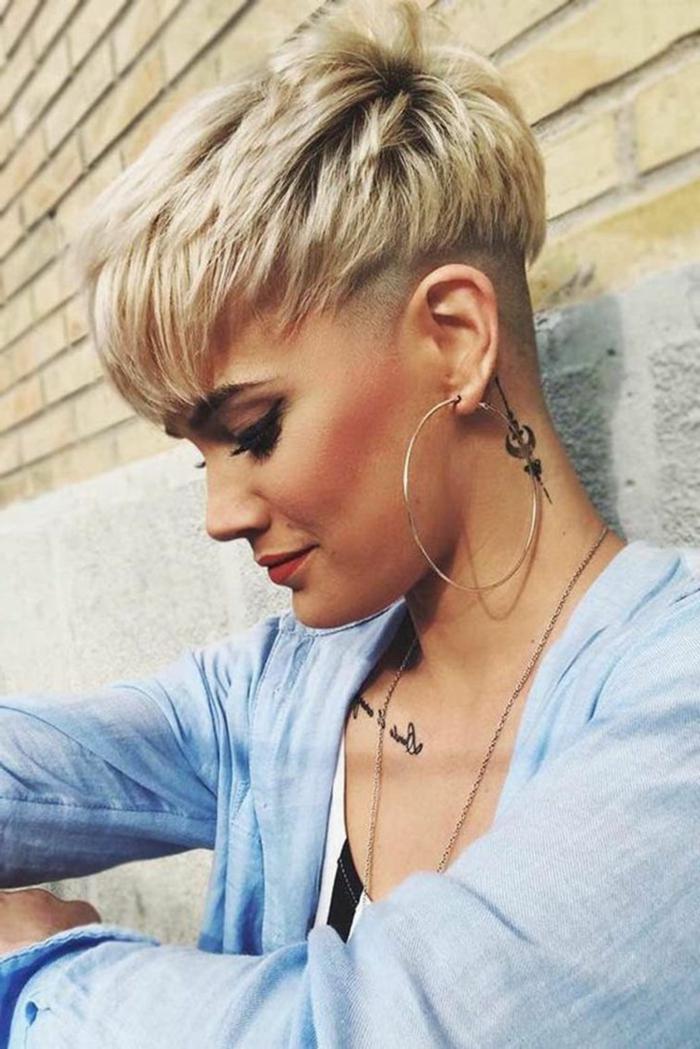 freche kurzhaarfrisuren undercut, große Creolen, Tattoo am Nacken, blonde Haare, blaue Bluse