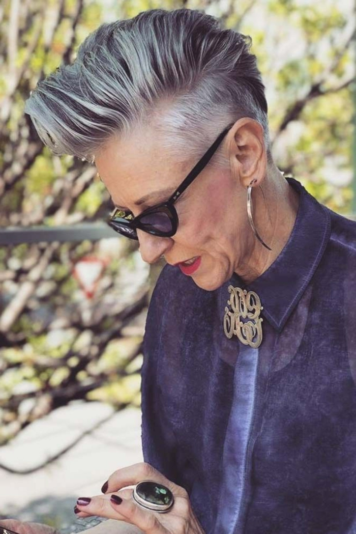frisuren für kurze haare, Pixie mit Undercut, freche kurzhaarfrisuren undercut, Frau mit grauen Haaren, Outfit in Lila, effektvolle Ohrringe und dünne, schwarze Sonnenbrillen, großer Ring
