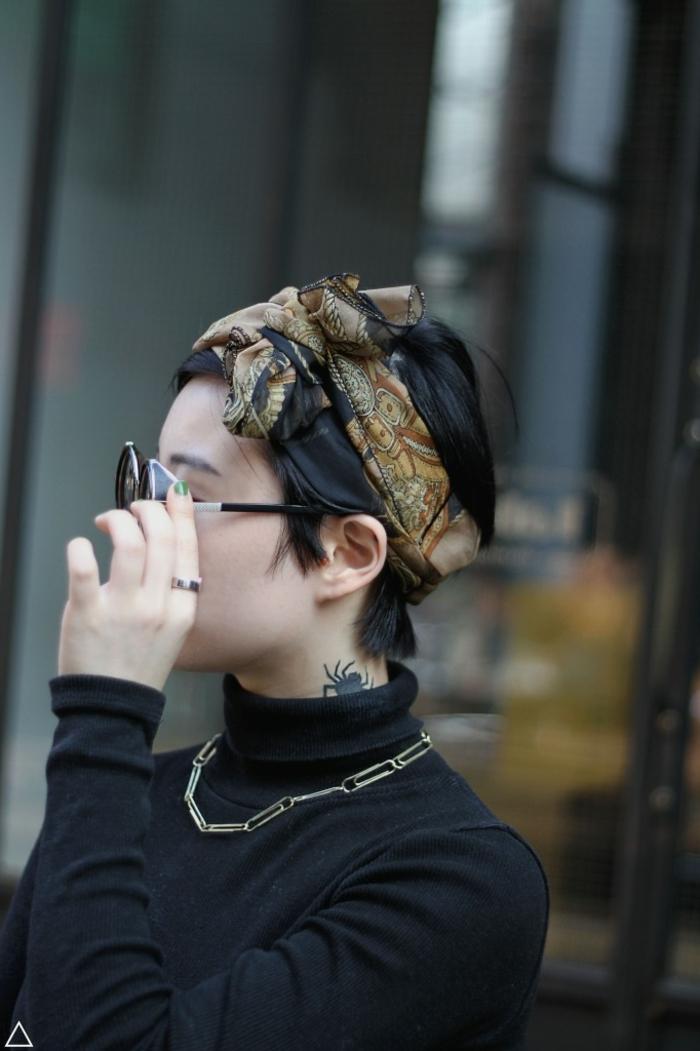 Frauen Kurzhaarfrisuren, schwarze Haare mit buntem Schal, große, schwarze Sonnenbrillen, Tattoo am Nacken von einer Spinne