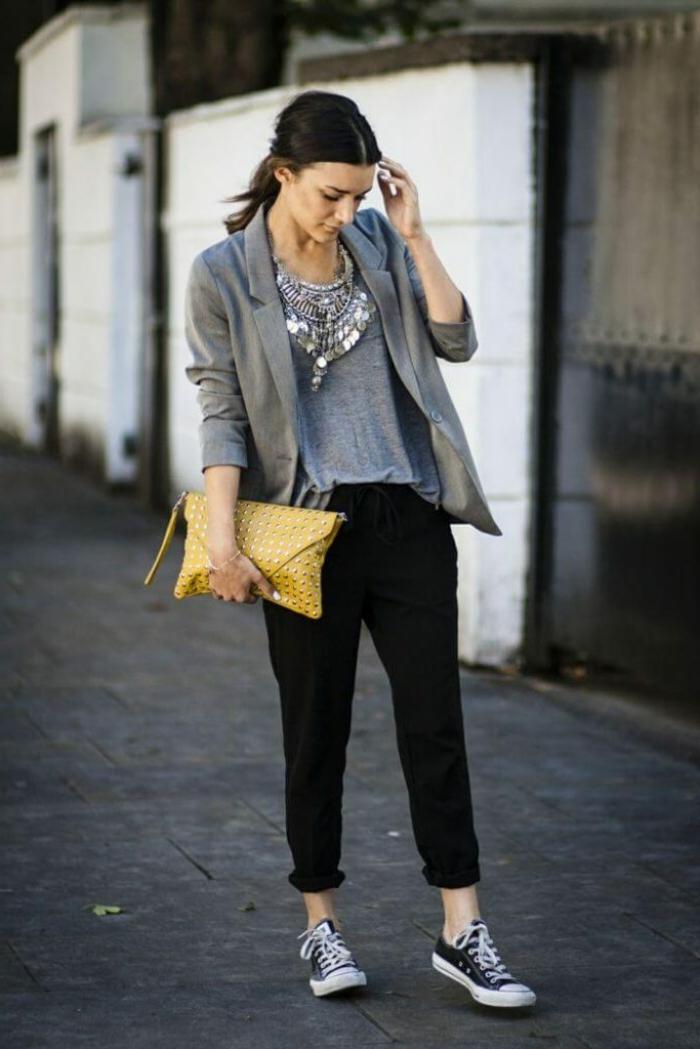Frau im casual outfit mit gelber Clutch aus Leder, schwarze Sneakers, graues T-Shirt und grauer Blazer