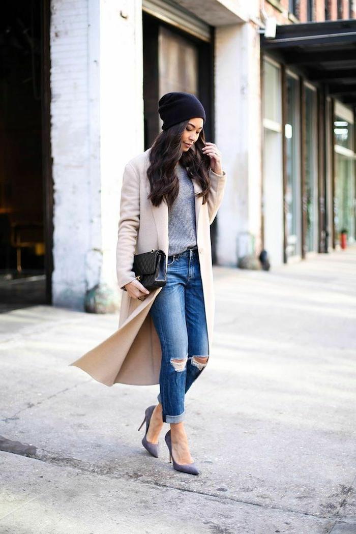 Elegant angezogene Frau im langen Mantel, zerrissene Jeans, Mütze dresscode leger