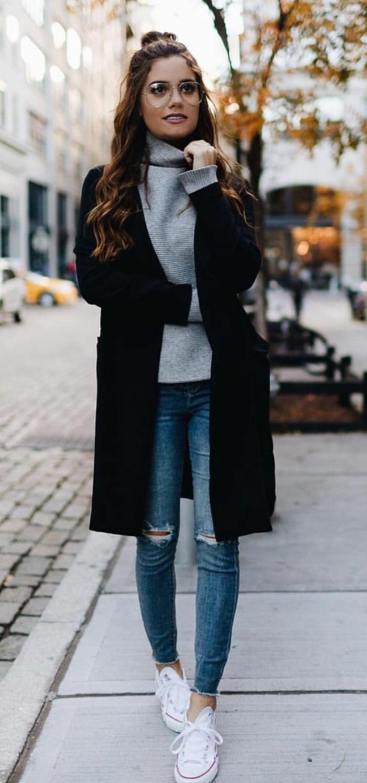 Sportlich angezogene Frau mit schwarzem Mantel, Rollkragenpullover und weiße Sneakers, smart casual women