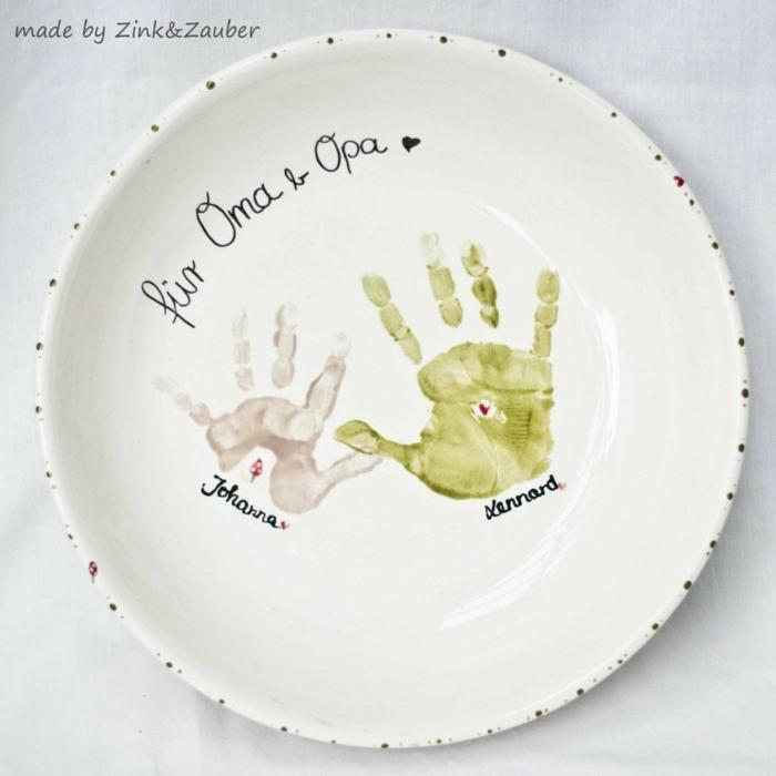 Geschenk für Oma basteln, weißer Teller mit Handabdrücken von Kindern, Aufschrift für Oma und Opa