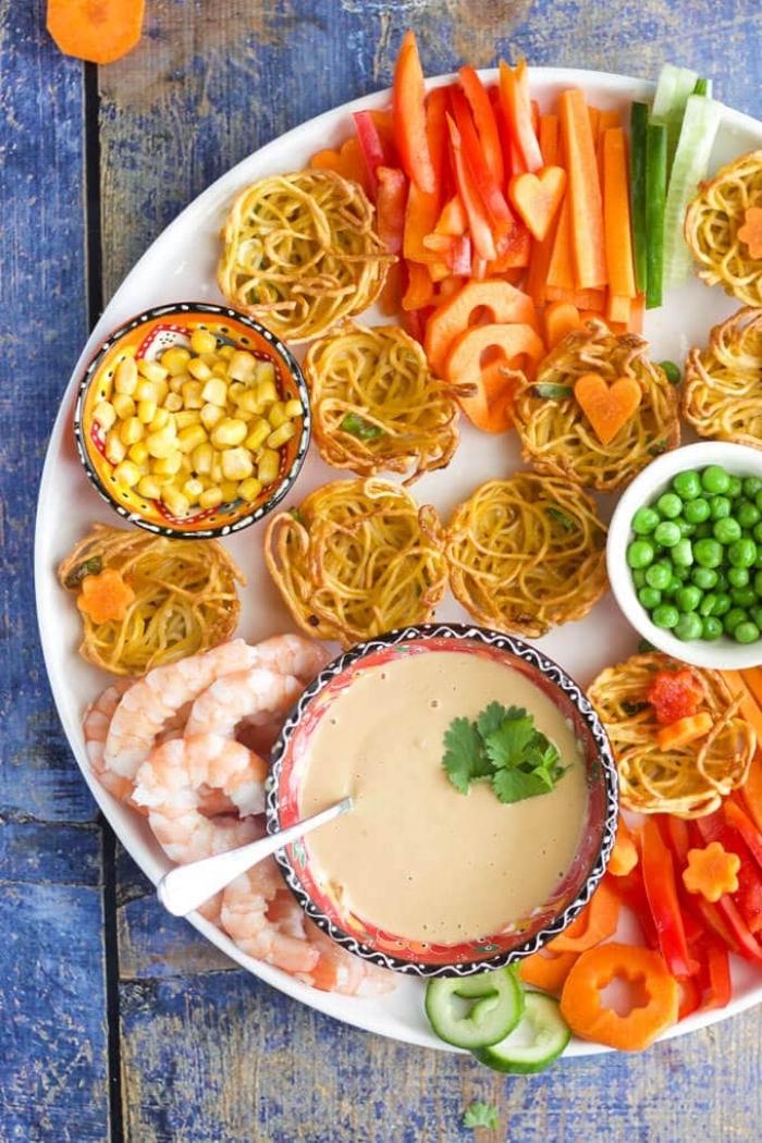 gesundes essen für kinder, geschnittene gemüse, nuddel chips, crmee soße, mais