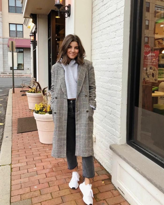 Dunkelhaarige Frau in langem Mantel mit Karo-Muster, weiße Sneakers, Jeans und Sweatshirt