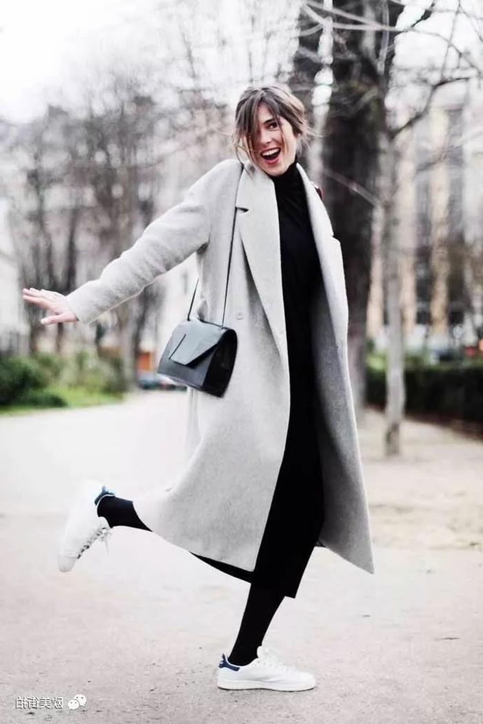 Lässig angezogene Dame mit langem Mantel, schwarzer Pullover, weißen Schuhen