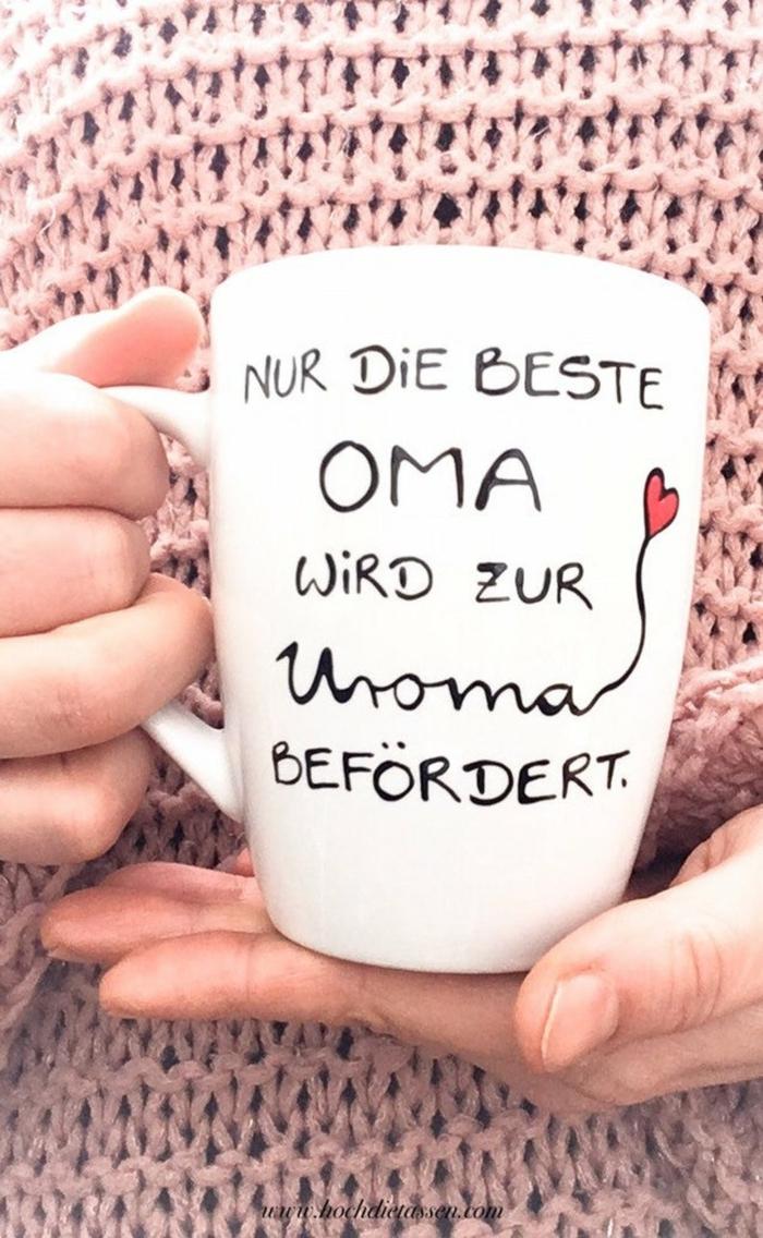 Tasse mit Aufschrift für Uroma, gemaltes rotes Herz, Hand hält Tasse, angezogen im pinken Pullover, Oma ist die Beste