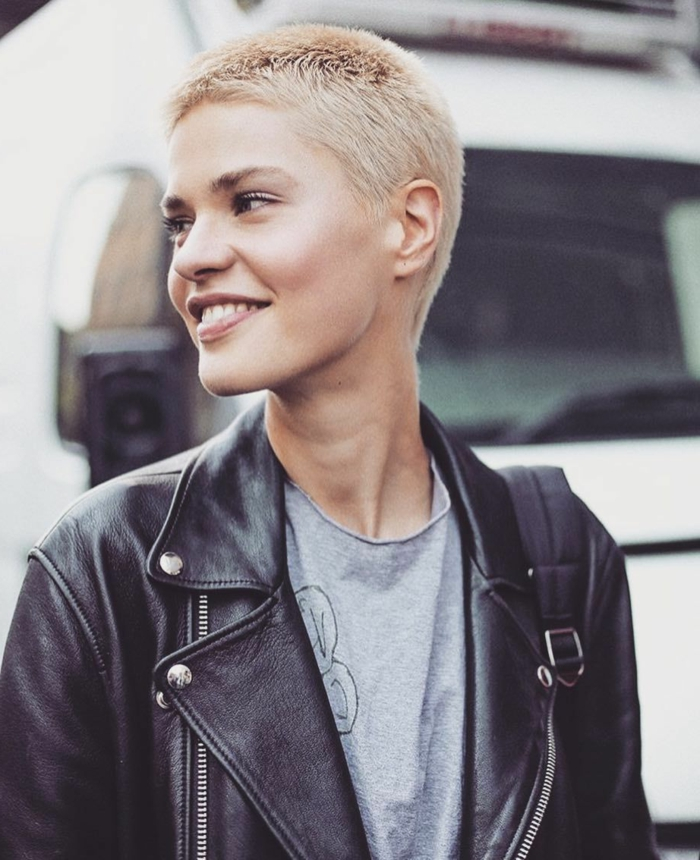 Blonde Frau mit Buzz Cut und minimalem Make-Up, Coole kurzhaarfrisuren damen, angezogen in schwarzer Lederjacke und graues T-Shirt