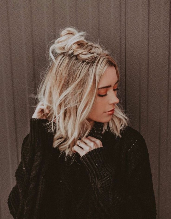 Frisuren Frauen kurz, blonde Haare halb hoch halb runter mit Zopf, geschminktes Gesicht, schwarzer Pullover, Foto am braunen Hintergrund,