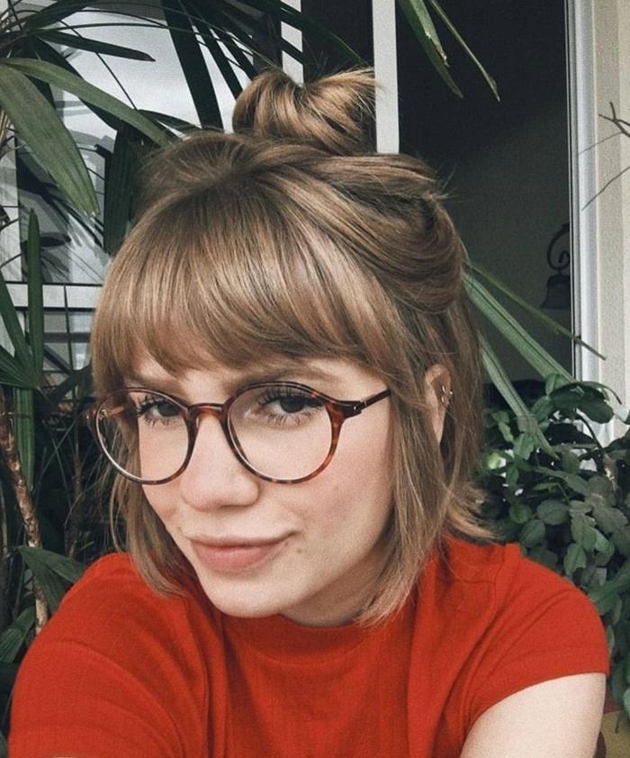 Kurzhaarfrisuren mit Brille, dunkelblonde Haare halb hoch halb runter mit messy Haarknoten, rotes T-Shirt, Pflanzen im Hintergrund