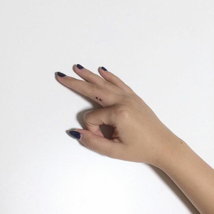 Semicolon Tattoo am Mittelfinger einer Hand mit dunklem Nagellack, tattoo psychische störung, weißer Hintergrund