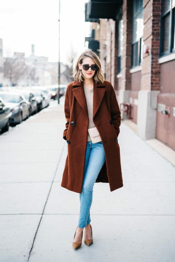 Dame mit dunkelrotem Mantel, Jeans in heller Farbe, braune Pumps und hellpinke Tasche, dresscode leger