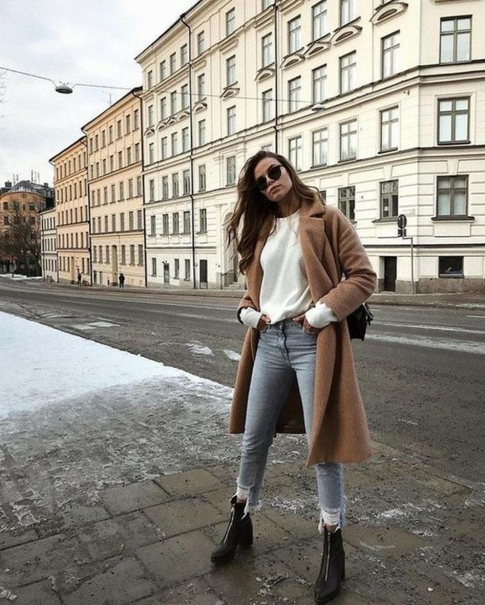 Casual angezogene Frau im braunen Cardigan, mit Bluse in heller Farbe und Jeans