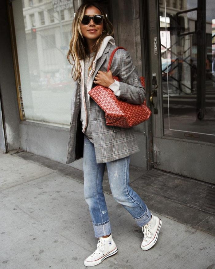Blonde Frau im Blazer mit Karo-Muster, lässige Jeans, rote Tasche aus Leder und Converse Schuhe, sportlich elegante outfits damen