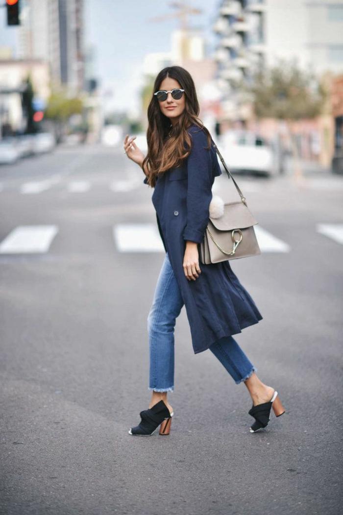 Elegant angezogene Frau mit langem Trench, effektvolle Schuhe, gerade Jeans, dresscode leger