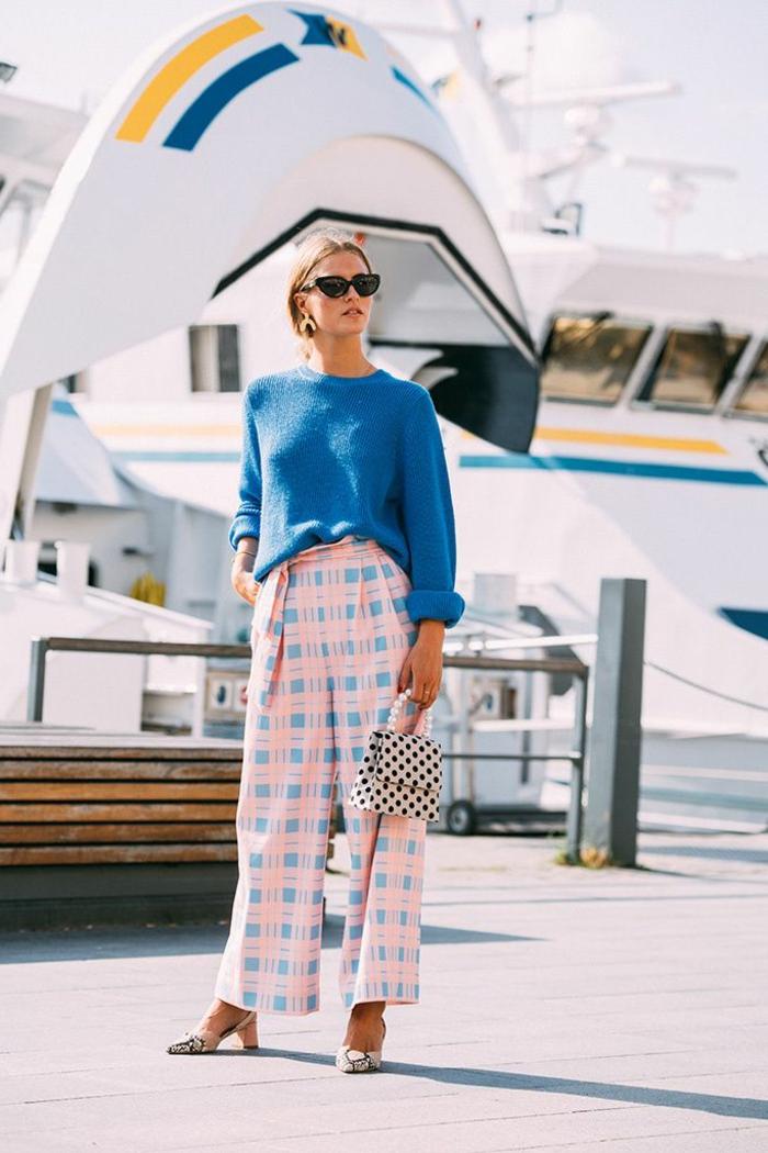 Effektvoll gestylte Frau, mit gemusterter Hose, blauem Pullover, Schuhe mit Absatz und kleiner Tasche, kleiderordnung casual