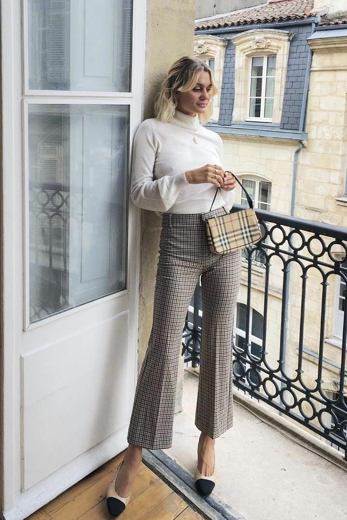 Elegante Dame in einer karierten Hose, einem weißen Oberteil, hautfarbene Pumps und mit kleiner Tasche
