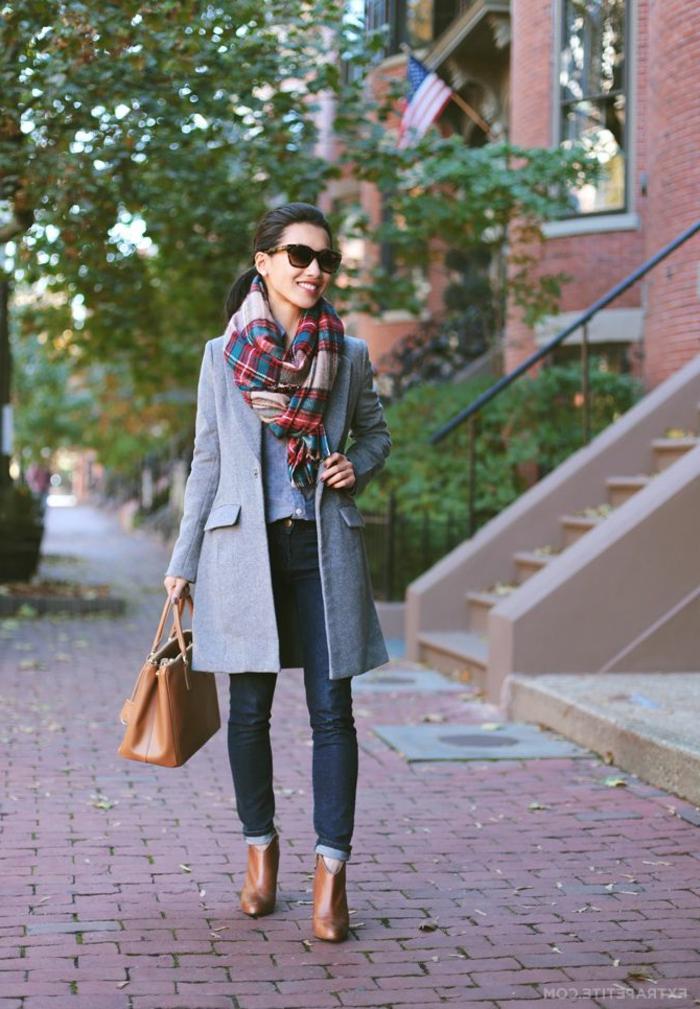 Elegante Dame mit grauem Mantel, buntem Schal, Tasche und Stiefel in Braun