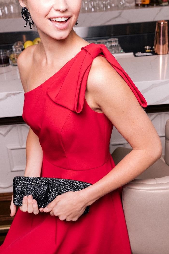 Elegantes Outfit für besondere Anlässe, rotes langes Kleid mit Schleife am Schulter, schwarze Clutch
