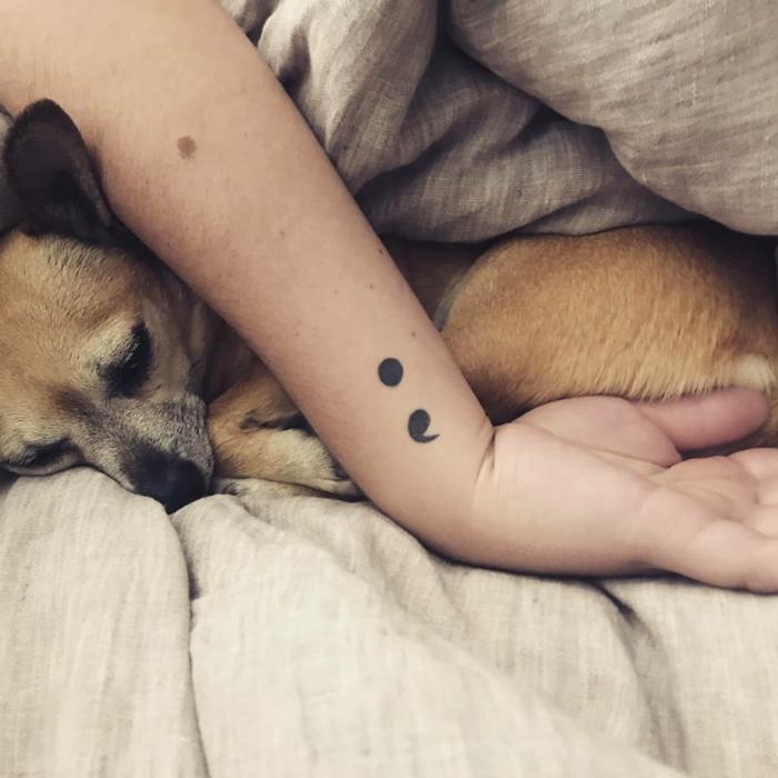 Hand mit einem Semicolon Tattoo und ein eingekuschelter Hund, zeichen für depression
