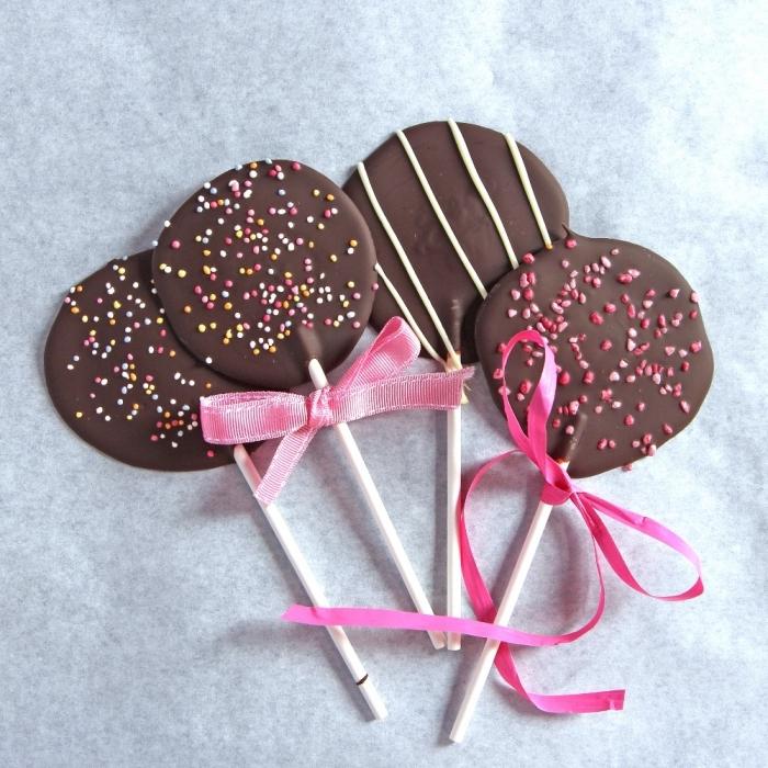 kochen mit kindern, einfache lutscher aus schokolade dekroiert mit rosa schleifen