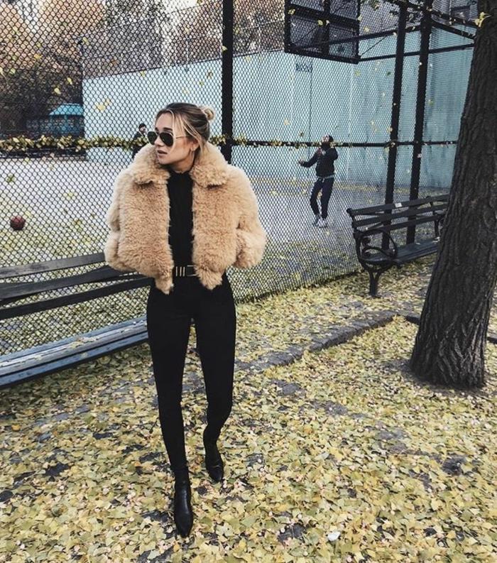 Dame im Herbst Outfit, mit schwarzen Jeans, Stiefletten und kurze, flauschige Jacke, kleiderordnung casual
