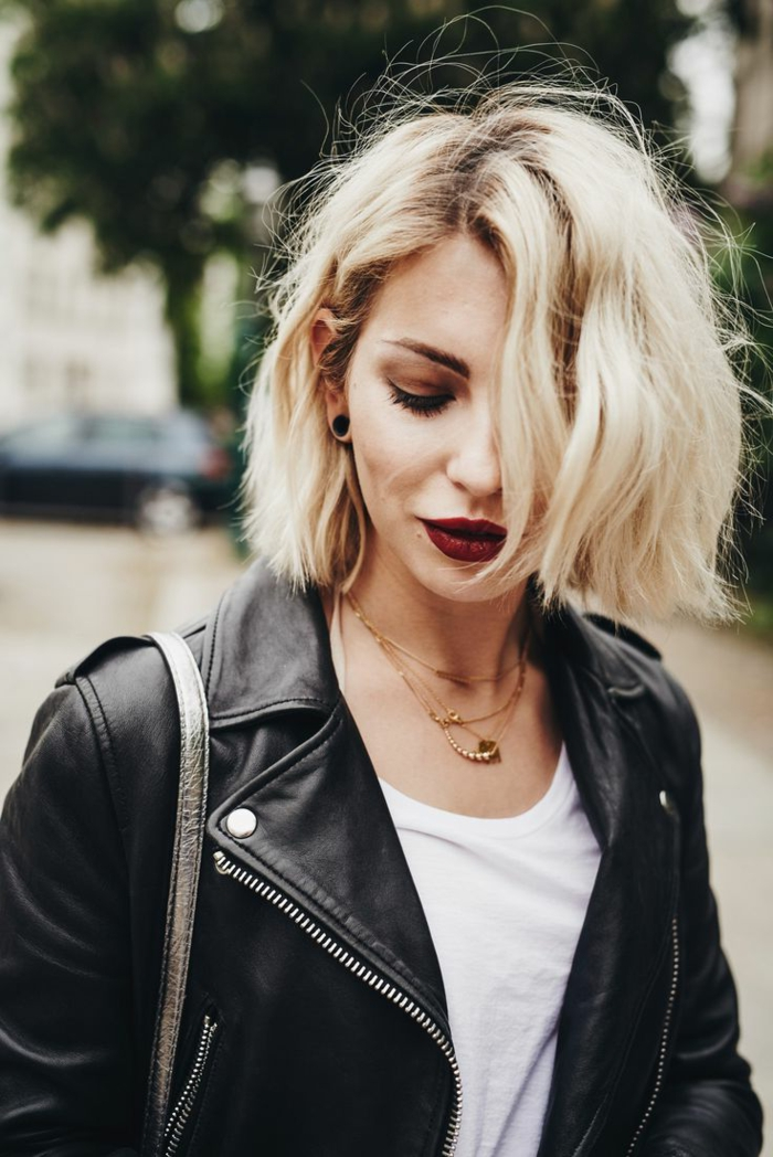 blonde Frau mit kurzem blonden bob haarschnitt, damenfrisuren kurz, schwarze Lederjacke mir weißem T-Shirt, geschminktes Gesicht mit dunkelrotem Lippenstift