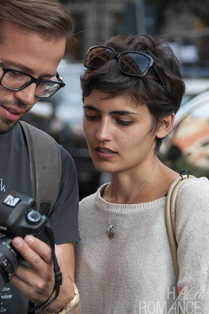 damenfrisuren kurz, street style Fotografie, Fotograf mit Kamera, schwarze Sonnenbrillen, weißer Pullover und Halskette
