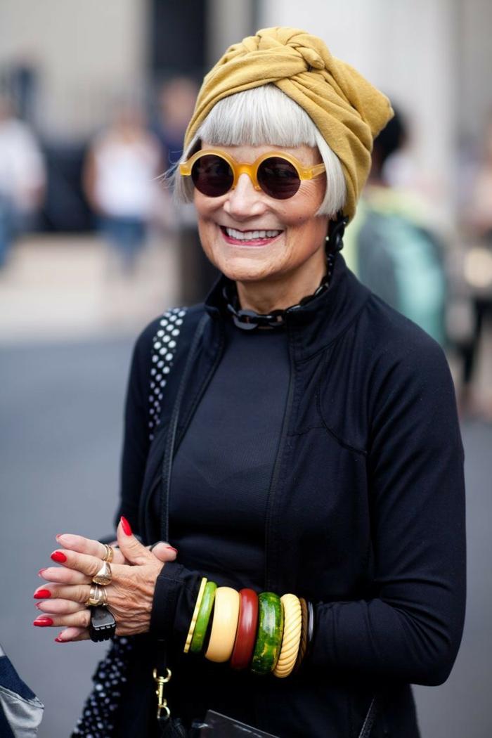 Modische Kurzhaarfrisuren, schwarzes Outfit, akzentuiert mit großen, bunten Armbändern, frisuren für kurze haare, weiße Haare mit kurzen Pony und gelber Turban, roter Nagellack und viele Ringe