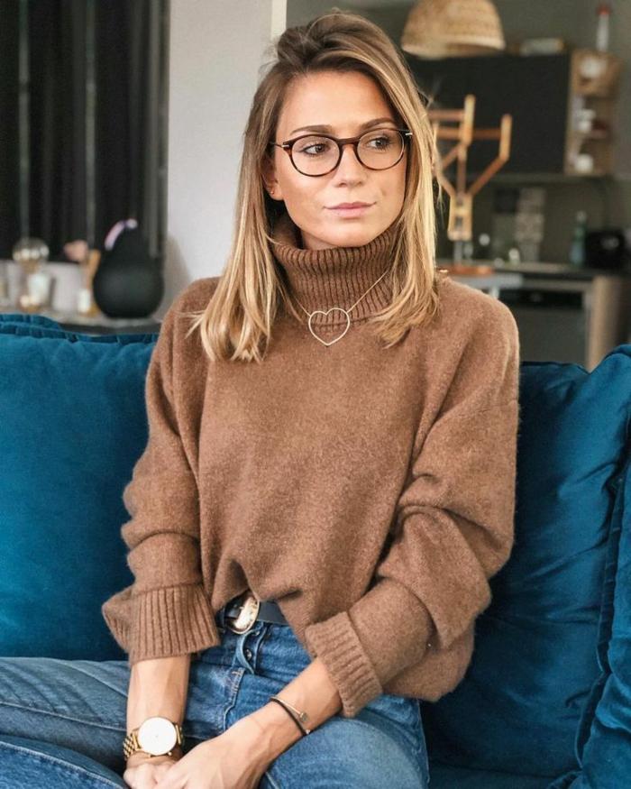 Kurzhaarfrisuren mit Brille, blonde Frau im braunen Pullover und Jeans, Halskette in Herzform, Sofa in blau, Uhr in Gold