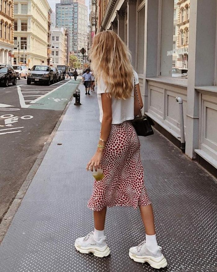 Dame im Sommer Oufit mit farbigem Rock, basic weißes T-Shurt und weiße Sneakers, business casual damen knigge