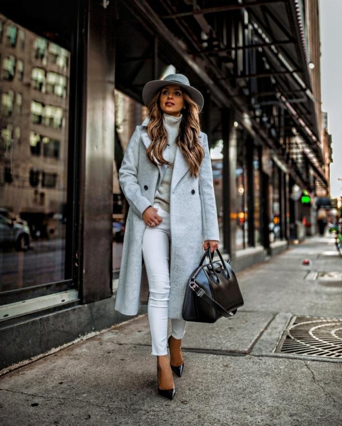 Dame im grauen, monochromen Outfit, langer Mantel, weiße Jeans und schwarze Tasche