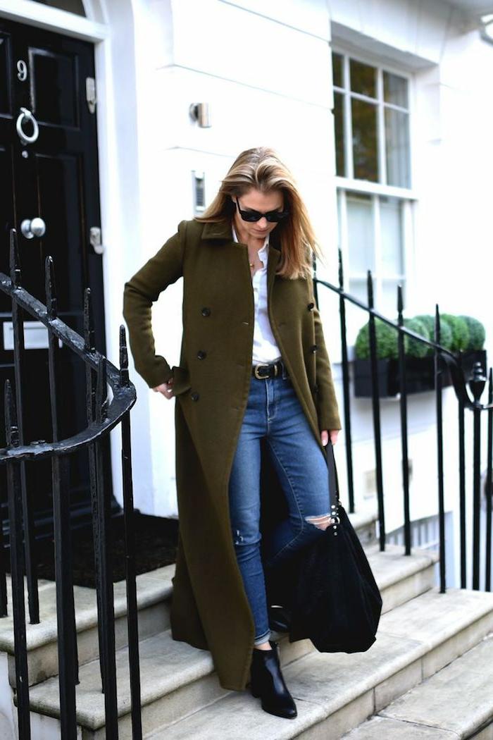 Elegante Dame mit einem bodenlangen Mantel, klassische Jeans, weißes Oberteil und Maxi-Handtasche