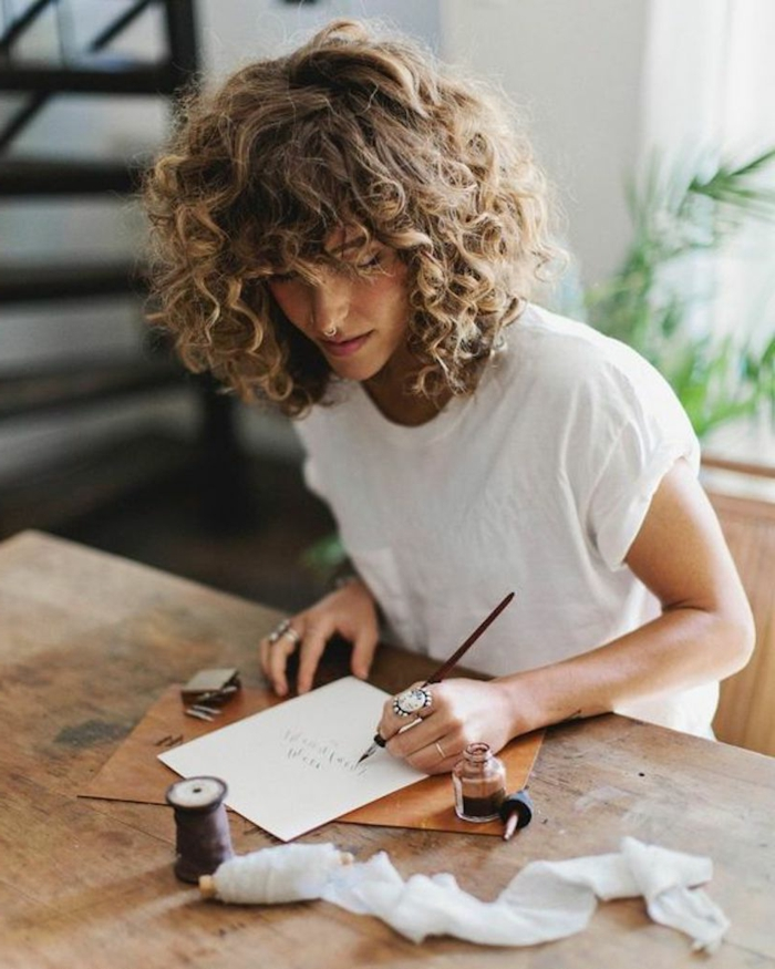 frisuren fraune kurz, lockige blonde haare mit pony, frau sitzt am tisch und schreibt, ring am finger, tisch aus holz, tinte und schreibfeder am tisch