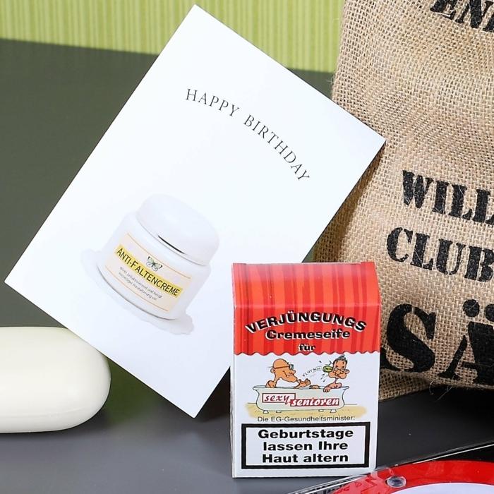 Seife in einer Zigarettenschachtel, mit lustiger Beschriftung, Abbild von Senioren in der Badewanne, Geburtstagskarte mit Abbild von Anti-Faltencreme