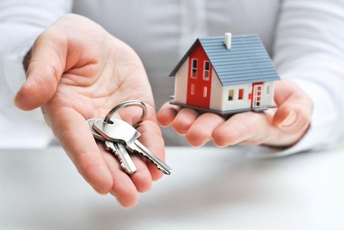 ein haus und hand mit schlüsseln, immobilienverkauf