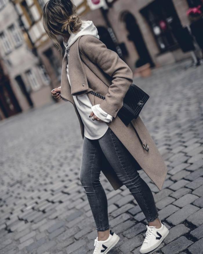 Dame in einem beigefarbenen Mantel, Hoodie, Skinny Jeans und weiße Sneakers, smart casual women