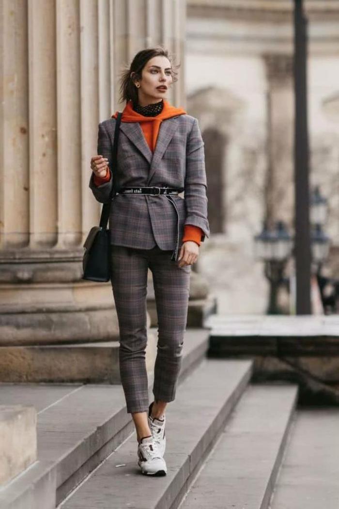 Frau im karierten Anzug mit einem orangenen Sweatshirt, schwarze Handtasche und Sneakers