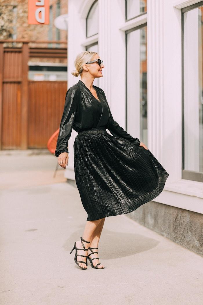 Schwarzes A-Linien Kleid mit langen Ärmeln und V-Ausschnitt, schwarze Pumps, blonde gebundene Haare
