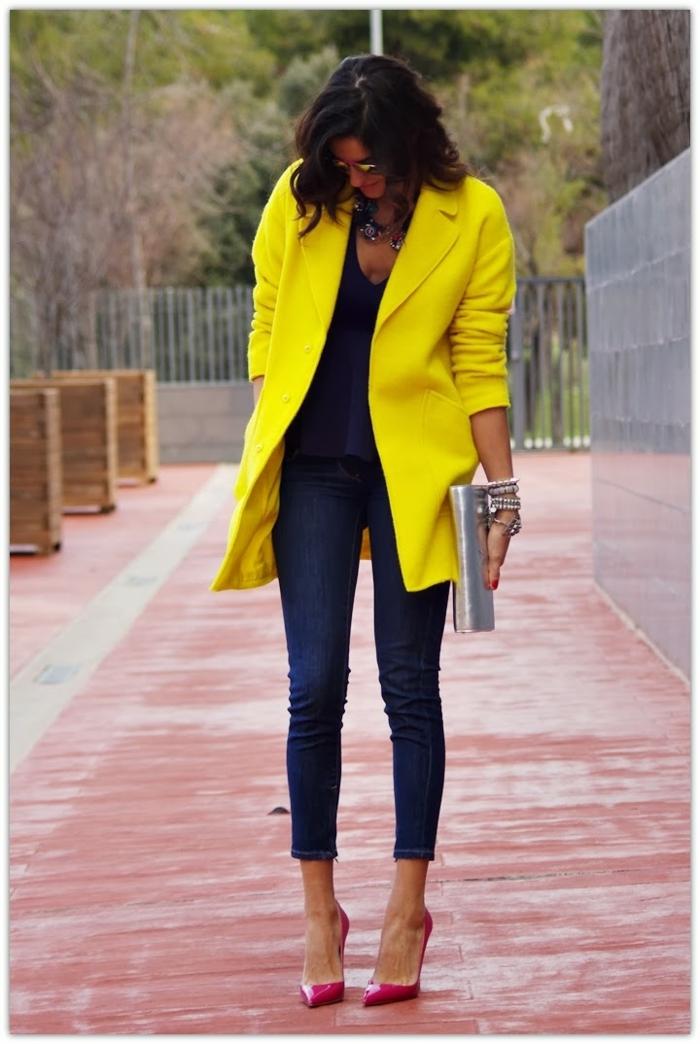 Große, dunkelhaarige Dame in Jeans, gelber Mantel, pinke Pumps, trägt ein Clutch