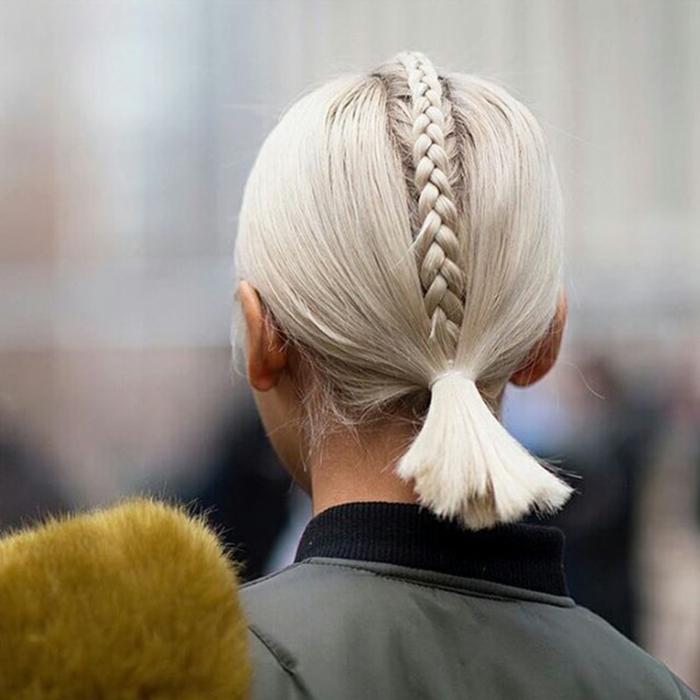 coole kurzhaarfrisuren, platinblonde Haare im Pferdeschwanz und Zopf in der Mitte, grüne Jacke